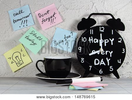cup black coffee with an alarm clock and stickers on a wall