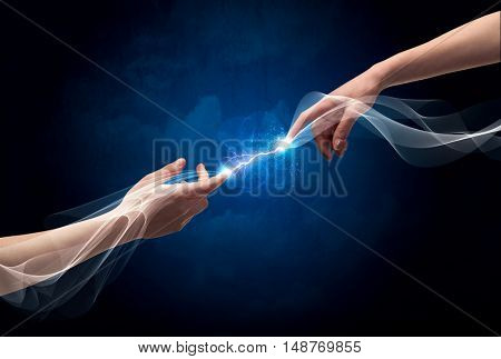 Two male arms reaching for each other, with a smoking electric current connecting their fingers in empty space background concept
