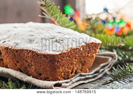 cake with raisins sprinkled with icing on a wooden table with Christmas tree and Christmas lights.