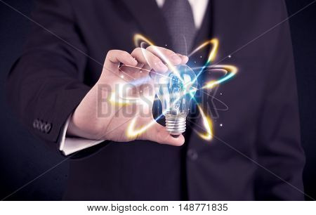 A classy businessman holding a colorful light bulb with shining circles in front of dark background concept.