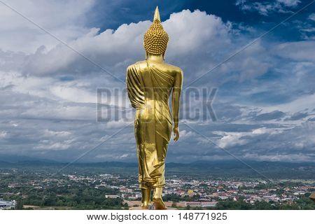 Buddha statue public landmark at Wat Phra that Kao Noi with dramaric clouds Nan Thailand