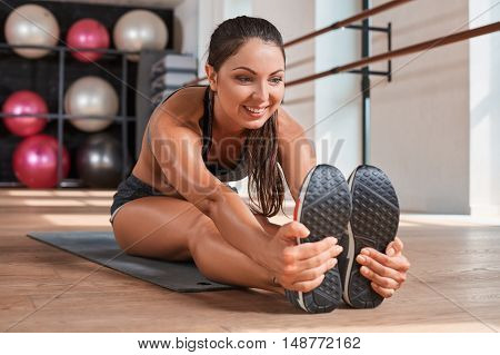 Gorgeous suntanned brunette doing exercises a the gym. girl doing stretching on the mat