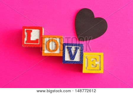 Valentine's Day.Love Spelled with colorful alphabet blocks and a black heart isolated on a pink background