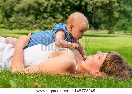 Mother And Her Baby Lying On The Grass In Park