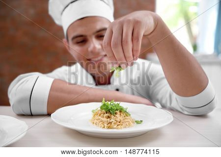 Young handsome chef cook preparing pasta in kitchen