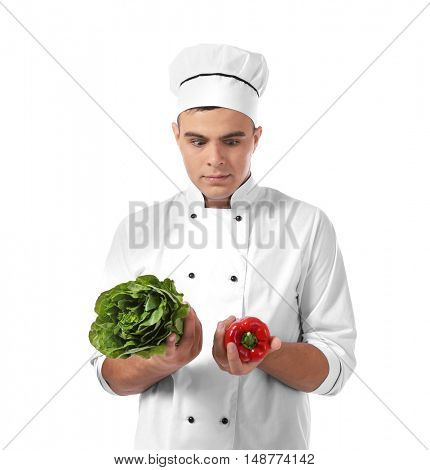 Young handsome chef cook with fresh vegetables isolated on white
