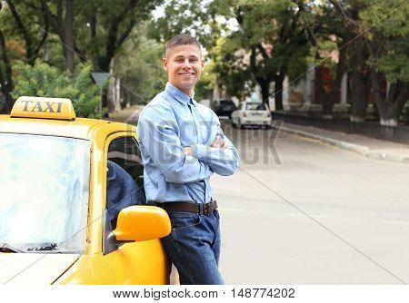 Male taxi driver near car