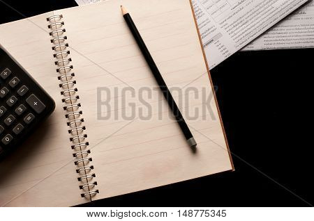 Stationary, Notebook, pencil and calculator use in business office black background