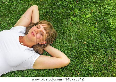 Woman Relaxing Outdoors And Lying On Grass In Park