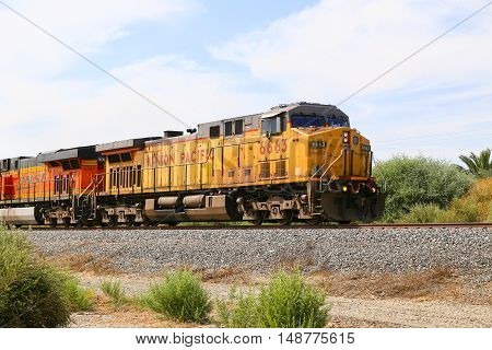 MECCA, CALFORNIA, USA - MAY 26, 2015: Freight train with both Union Pacific and BNSF engines on track next to California State Route 111.