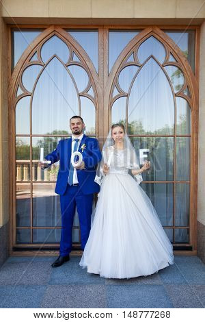 Newlyweds are holding the letter in his hands on a photo shoot on the wedding day