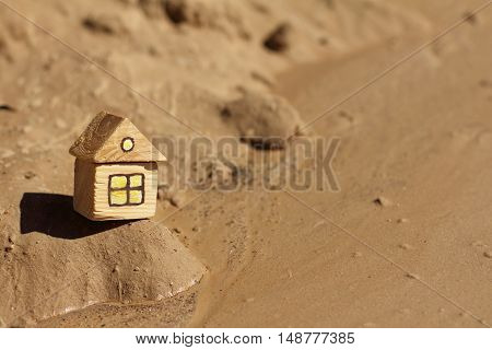 small wooden house standing on a sandy landscape under a blazing sun / hot days of global warming