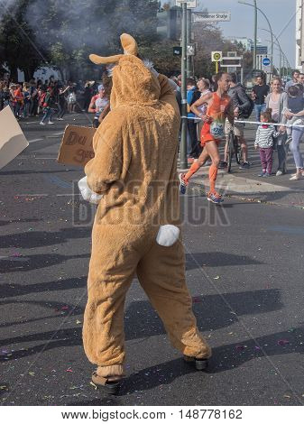 BERLIN GERMANY - SEPTEMBER 25 2016: Spectator With A Rabbit Costume And Runners At Berlin Marathon 2016
