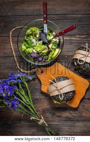 Delicious black burgers salad and blue flowers on dark wood table.