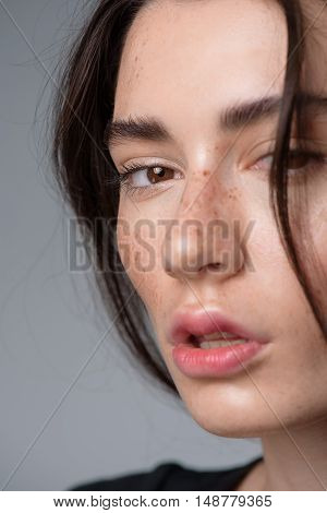 skincare and beauty concept, close up of a attractive freckled woman looking into camera