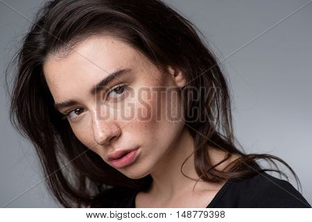 skincare and beauty concept, close up of a serene young woman looking into camera