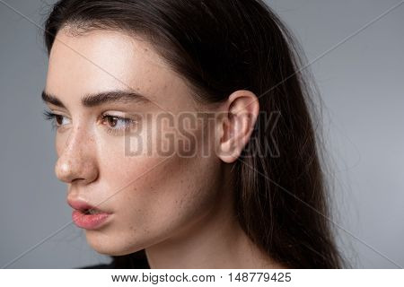 skincare and beauty concept, portrait of a quiet beautiful freckled girl looking into camera