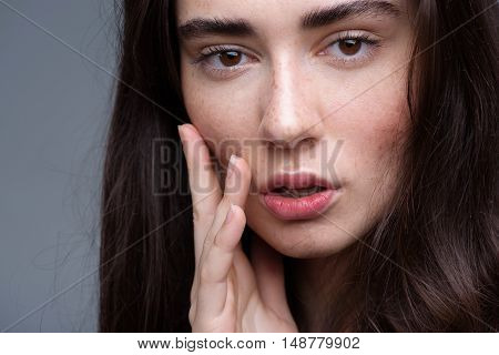 beauty and skincare concept, portrait of a calm peaceful freckled brunette looking into camera