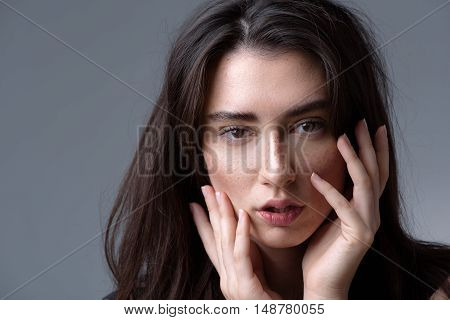 beauty and skincare concept, face of a peaceful beautiful brunette isolated on light grey background with copyspace