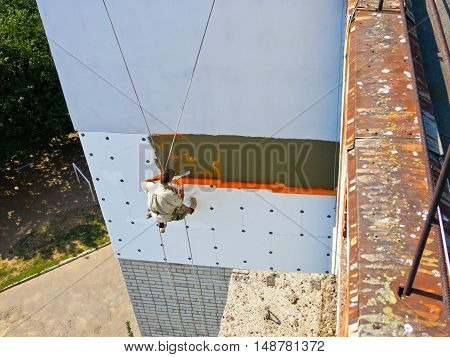 Rope access worker makes up the insulation of the apartment with the polystyrene