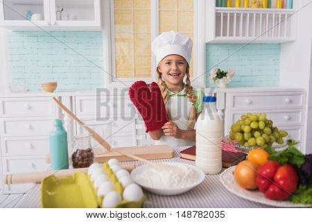 Pretty girl is ready to cook. She is wearing potholder and smiling. Kid is standing and looking at camera with happiness