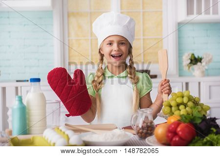 Happy little girl is holding wooden spatula and oven-glove with preparation. She is standing in kitchen and laughing