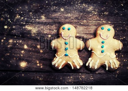 Christmas homemade gingerbread man cookie on wooden table with decorations. Christmas Holiday Background with snowflakes