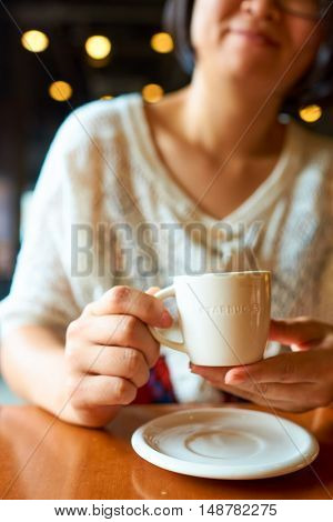 SHENZHEN, CHINA - SEPTEMBER 07, 2016: a woman hold cup with espresso at Starbucks in Shenzhen. Starbucks Corporation is an American coffee company and coffeehouse chain.