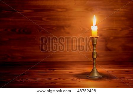 Burning Old Candle With Vintage Brass Candlestick On Wooden Background In Minimalist Room Interior,