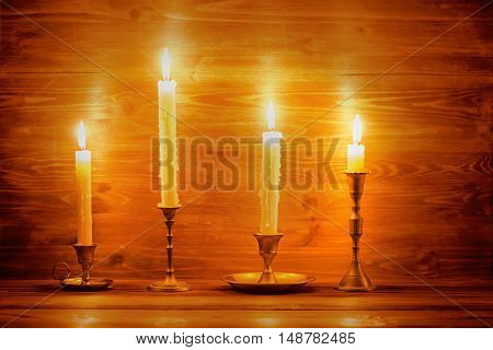 Beautiful Four Candles With Different Vintage Candlesticks On Wooden Background, Close Up
