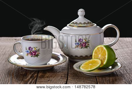 Teapot and teacup, tea drinking with lemon