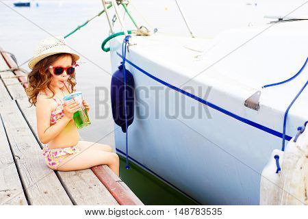 little girl in red sunglasses and bathing suit drinking sparkling water on the pier at the lake
