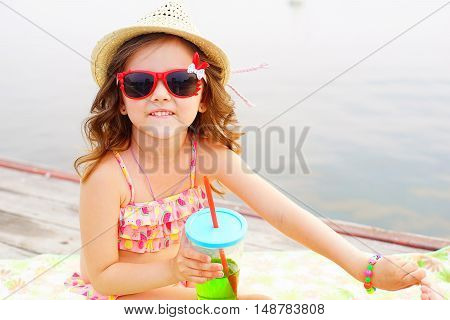 little girl in red sunglasses and bathing suit with sparkling water on a pier at the lake