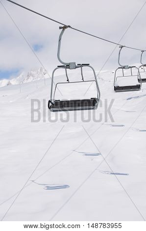 empty free chair ski lift on the snowboard resort with shadows on white snow background. Copy space for advertising.
