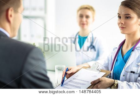 Medical team sitting at the table in modern hospital .