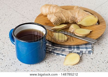 The enamel mug with hot tea, ginger root and knife on the cutting board, on the kitchen table.