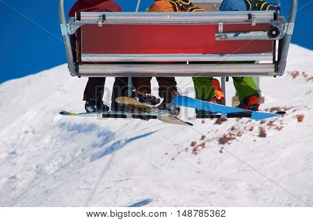 Snowboarders legs on the lift on ski resort in winter season. Copy space for advertising. Extreme sport concept or family relax for weekend.