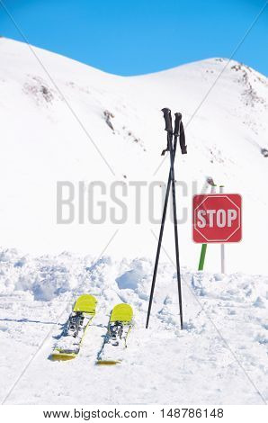Winter extreme sport concept. Pair of cross skis on snow. Sign stop on ski resort high in mountains. Place for freeride with powder.