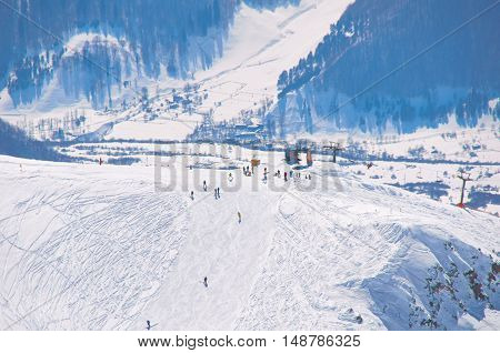 Bird view on peak of ski resort with ski riders and snowboarders. High point in mountains. Extreme active sport concept for healthy people. Place for holiday and weekend.