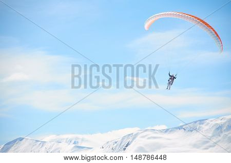 Paragliding high in mountains in blue bright sky. Tandem fly above peaks snowy peaks in sunny day. Extreme sport life.