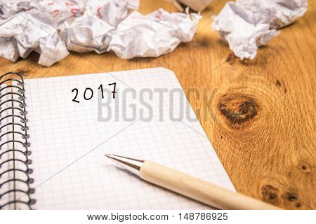 The 2017 new year concept - New year concept with 2017 written on a graph spiral notebook and crumpled pages in the background suggesting the passing of years.