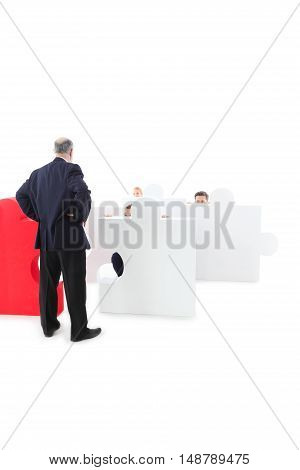 Business people hiding behind puzzle pieces on white