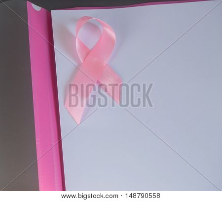 Pink ribbon on a piece of paper to raise awareness breast cancer, copy space.