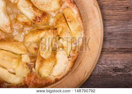 Overhead view of a freshly baked Tarte Tatin, a traditional French dessert made with puff pastry and sliced apples. Space for text.