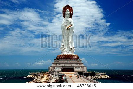San Ya (Hainan) China - May 15 2009: Set on a small man-made island in the sea the 108 meters high Bodhisattva Guan Yin Chinese Buddhist Goddess of Mercy the 4th largest statue in the world is reached by a stone walkway *