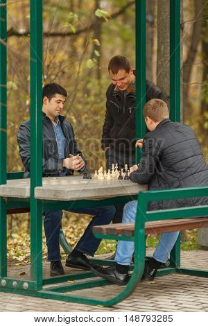 Two young men in black jackets playing chess, outdoors in park, third man watching them play