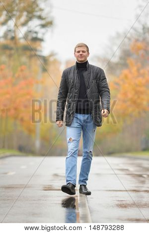 young man in black jacket and blue jeans walking along alley in park