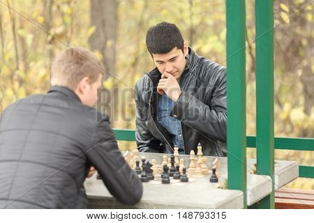 Two young men in black jackets playing chess outdoors in park