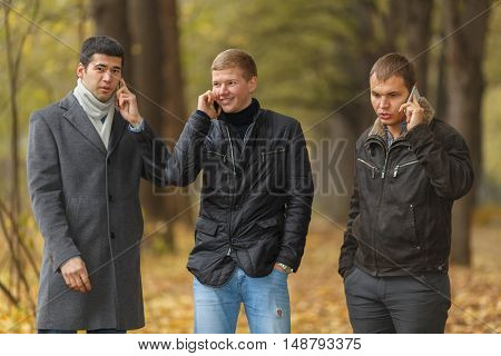 Half growth portrait of three young men in autumn park talking on phone