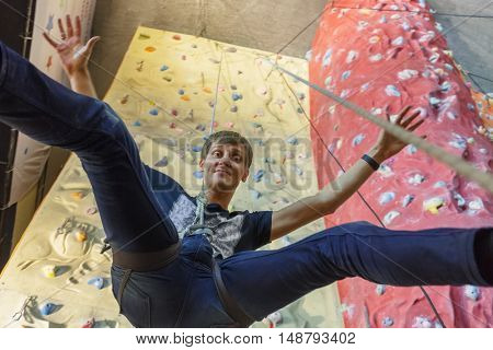Rock climbing. male climber hanging on tether on background wall climbing, view from below.